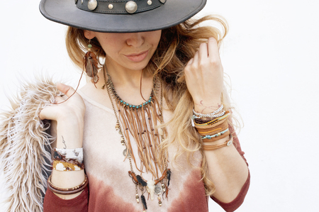 Fashion woman portrait, hands with boho chic bracelets, leather necklace and hat, outdoor fashion photo