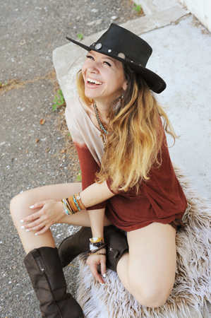 Fashion woman portrait, dreesd in leather hat, hands with boho chic bracelets, leather necklace