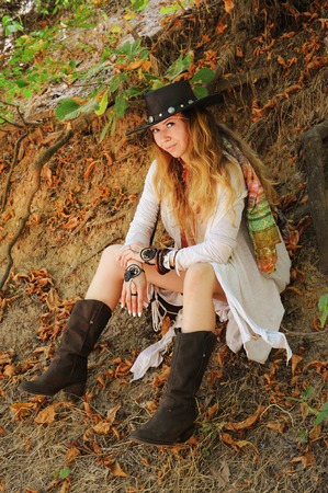 Beautiful female portrait dressed in dreamcatcher bracelets and black leather hat, indie style, outdoor Stock Photo