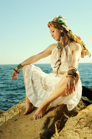 Fashion woman portrait with headband and handmade necklace and earrings, sunny backlit outdoor photo, boho chic style