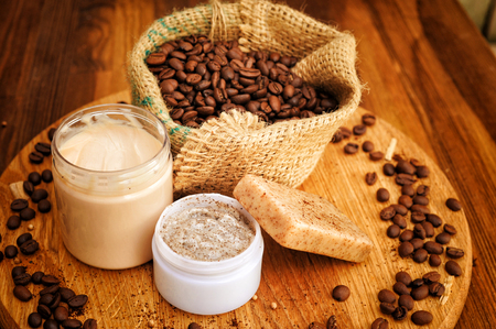 Authentic background with handmade coffee cosmetics - soap, cream and scrub and coffee beans in burlap sack