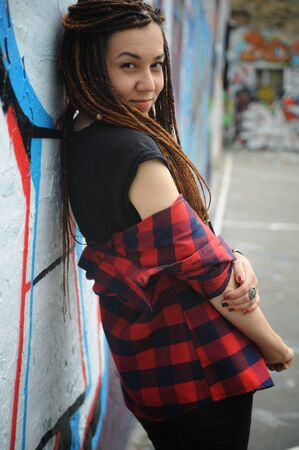 Smiling young woman portrait with dreadlocks, against graffiti
