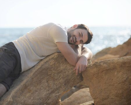 Young handsome man outdoor portrait lying on a rocks and smiling