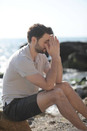 Depressed sad young man sitting on a sea beach, palms on face