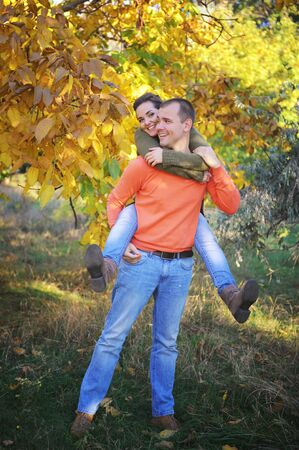 Young happy love couple in autumn park, smiling man and woman rest outdoor, family relax Фото со стока