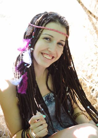 Indie style young woman with dreadlocks portrait, outdoor in autumn park, looking at camera
