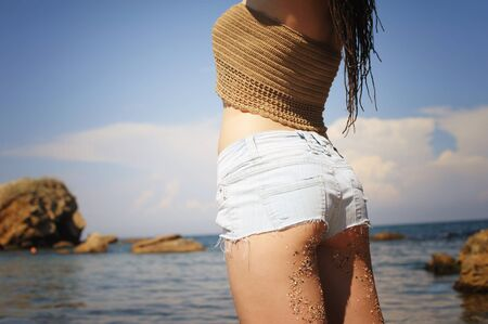 Woman buttock dirty with sand against sunny seascape, boho chic style, indie style, enjoy summer vacations 写真素材