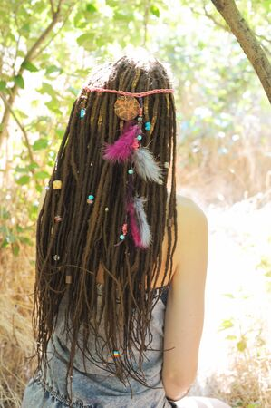 Beautiful young woman with dreadlocks hairstyle decorated assorted beads and colored feathers, sunny outdoor, no face