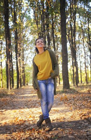 Young woman resting in autumn park, hiking, dressed in casual wear, look at camera and smiling