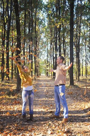 Young happy family toss the autumn leaves in park, smiling man and woman rest outdoor, family relax, love couple have a time together