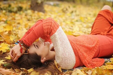Happy resting girl portrait, lying in autumn maple leaves in park, closed eyes, dressed in fashion sweater and many friendship bracelets, outdoor
