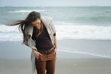 Young cute woman walking by a sea beach, windy day, autumn fashion, healthy lifestyle concept
