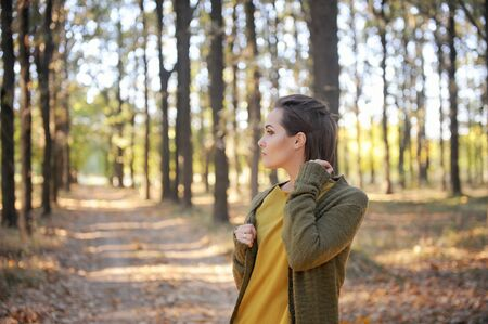 Young woman portrait outdoor in autumn park, dressed in casual wear Фото со стока