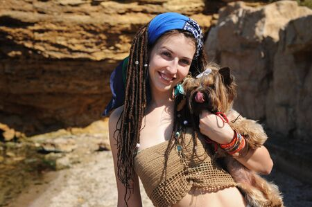 Smiling woman portrait with her yorkshire terrier dog, girl with dreadlocks