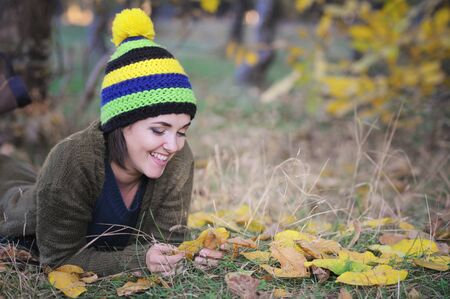 Young smiling woman portrait dressed in beanie hat with pom pom, resting in autumn park, outdoor