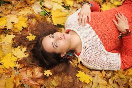 Uśmiechnięty szczęśliwy portret kobiety, leżący w jesiennych liściach, ubrany w modny sweter, jesień na zewnątrz