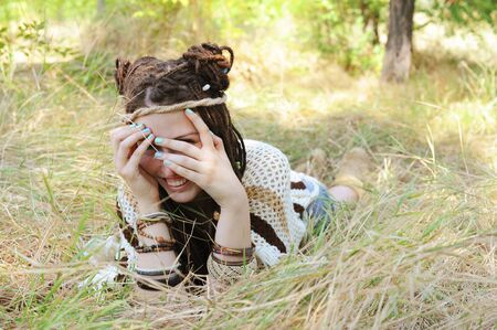 Joyful woman with dreadlocks hairstyle, have a fun closing her face with a hands, sunny autumn outdoor