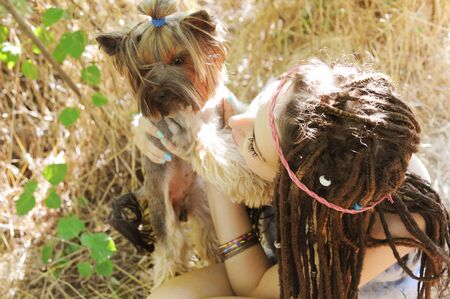 Happy hippie woman with her yorkshire terrier dog outdoor