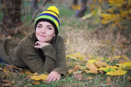 Smiling woman portrait dressed in beanie hat with pom pom, outdoor in autumn park Фото со стока - 129016522