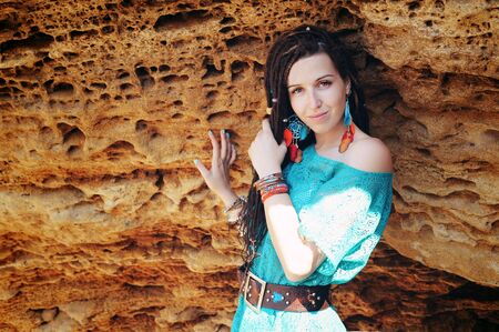 Portrait of a young smiling woman wearing dreadlocks hairstyle, dressed in blue lace dress and blue boho chic dreamcatcher earrings with leather feathers, posing against stone backdrop, looking at camera Фото со стока - 129016517