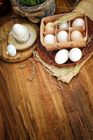 Organic raw chicken eggs in egg box against old style wooden background Фото со стока