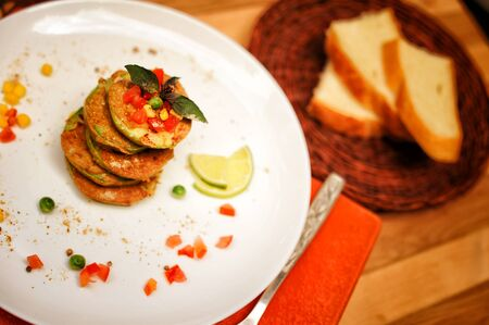 Squash fritters served on a plate and whole grain bread, top view