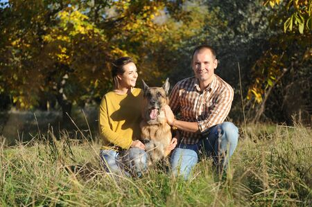 Happy love couple with their german shepherd dog, young family portrait, casual wear, outdoor
