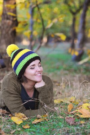 Happy smiling woman portrait, have a rest outdoor in park, dressed in knitted hat with pompom