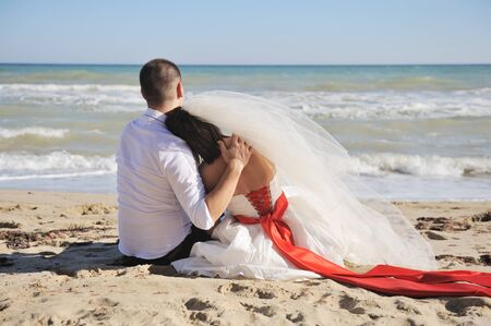 Cute wedding couple sitting on a sand on the beach, backs, no face Фото со стока - 131003278