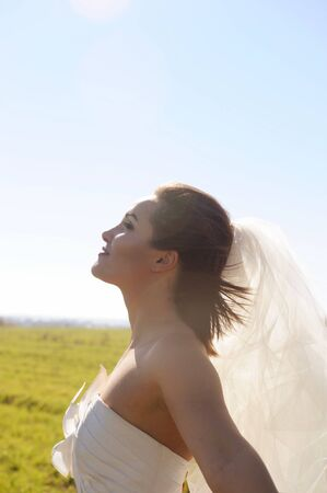 Pretty young bride profile portrait on a field, sunny backlite, windy weather