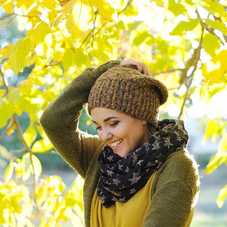 Young happy woman portrait, dressed in knitted hat and jersey, outdoor