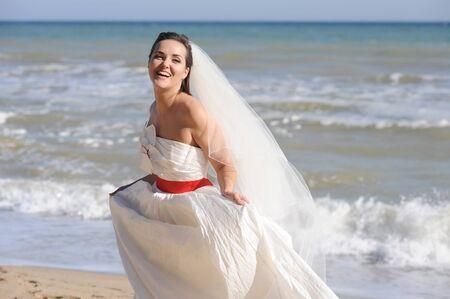 Joyful happy bride walking on a seacoast Фото со стока - 131003281