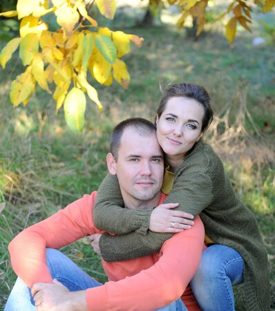 Young couple portraits outdoor in autumn park, family relax