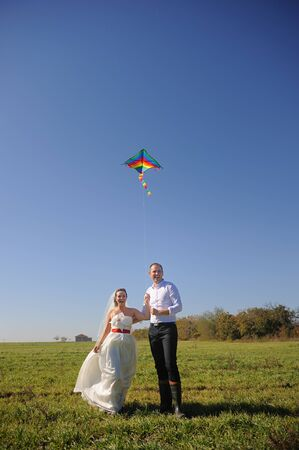Pretty young adult wedding couple walking on field with flying kite