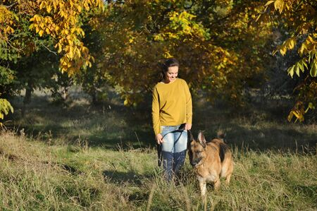 Young woman portrait with their german shepherd dog in autumn park, casual wear, outdoor Фото со стока