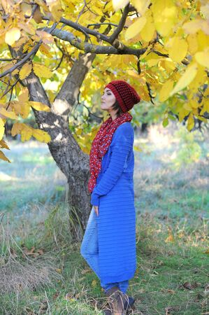 Young woman profile portrait, dressed in blue cardigan, outdoor in autumn park Фото со стока - 130989878