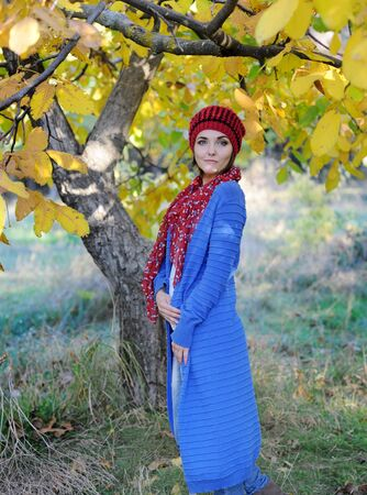 Beautiful smiling woman outdoor portrait, dressed in knitted beret and blue cardigan Фото со стока