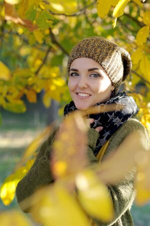 Young woman portrait, dressed in knitted hat, outdoor in autumn park