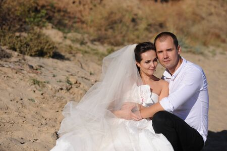 Wedding couple sitting on a sand, outdoor