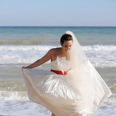 Pretty young bride walking on a sea beach Фото со стока - 130989929