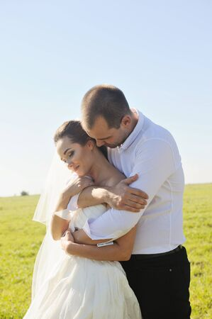 Happy married couple enjoying wedding day in nature, outdoor photo Фото со стока