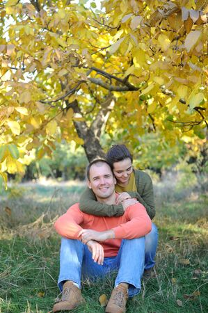 Young couple portraits, rest outdoor in autumn park, family relax, love couple have a time together