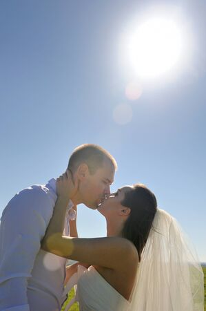 Happy married couple kissed and enjoying wedding day in nature, outdoor photo Фото со стока - 130997996