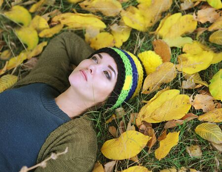 Depressed sad young woman lie in foliage, outdoor portrait, unhappy face Фото со стока - 130990054