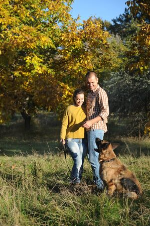 Happy love couple walking in park with their german shepherd dog, holding hands, young family portrait, casual wear, outdoor Фото со стока