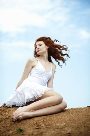 Cute young smiling female with red hair fluttering in the wind