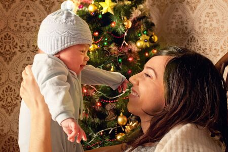 Mother and newborn baby at home near christmas tree