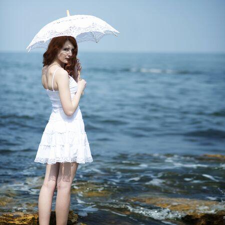 Girl in white dress standing near sea with white lace sun umbrella Фото со стока - 130990070
