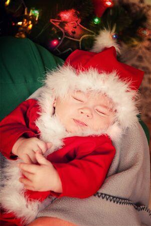 Beautiful sleeping newborn baby dressed in Santa Claus costume Фото со стока - 130997998