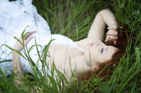 Young sleeping outdoor red hair woman, fashion portrait in white dress